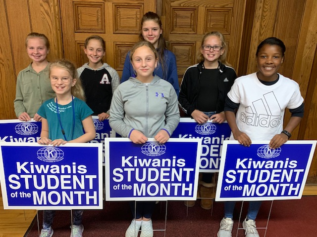 the selected students of the month are posed with their yard signs declaring they are a Kiwanis Student of the Month