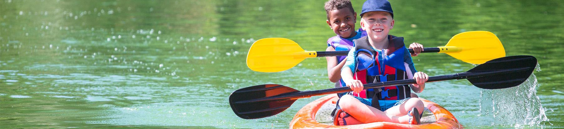 Two young smiling boys wearing multi-colored life vests while paddling in a orange kayak on a calm green lake