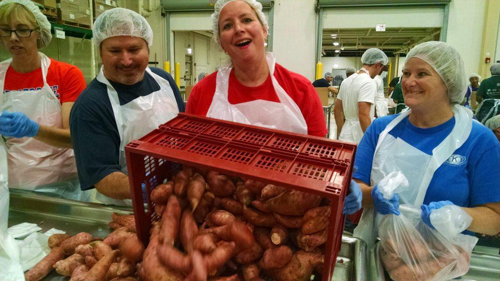 3 eKiwanis members sorting a crate of sweet potatoes