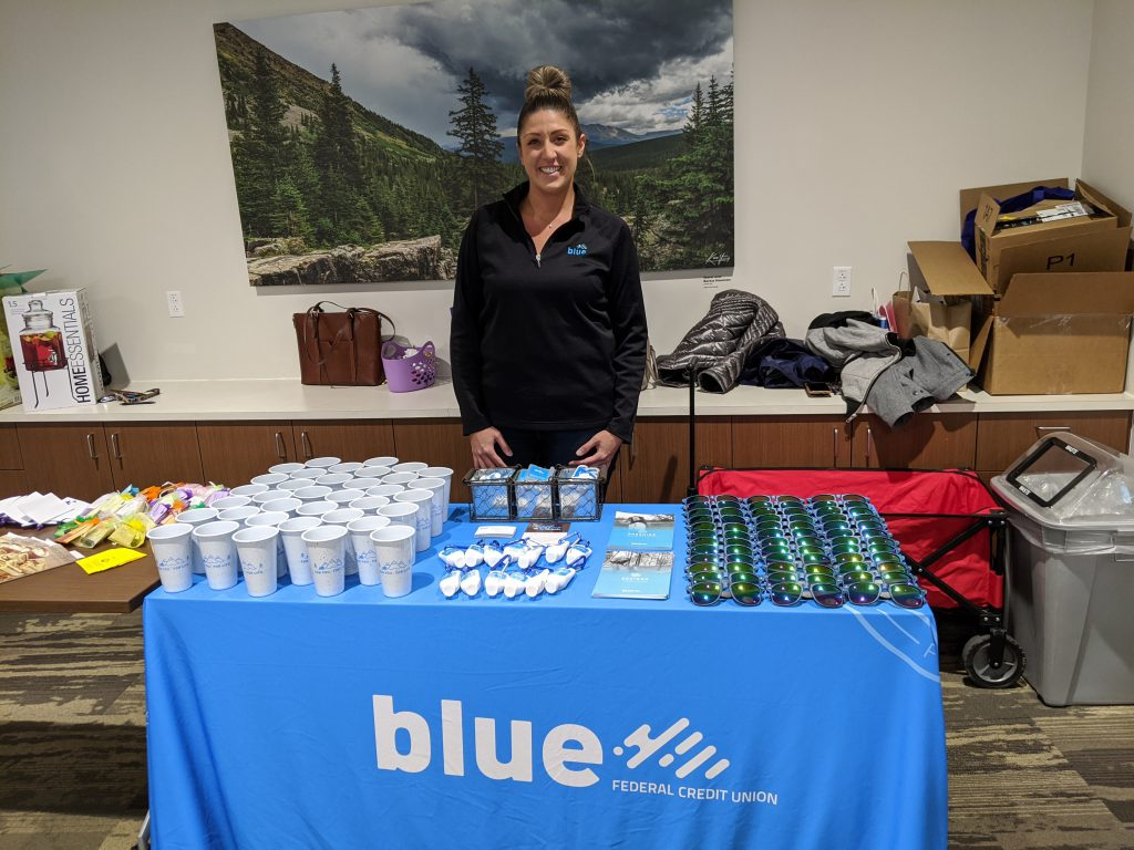Smiling woman behind Blue FCU table with gift items for an event
