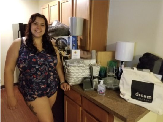 Smiling young lady in her first apartment with a kit of necessities