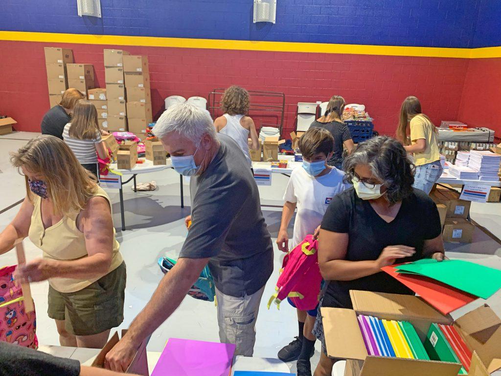 Volunteers filling backpacks with school supplies