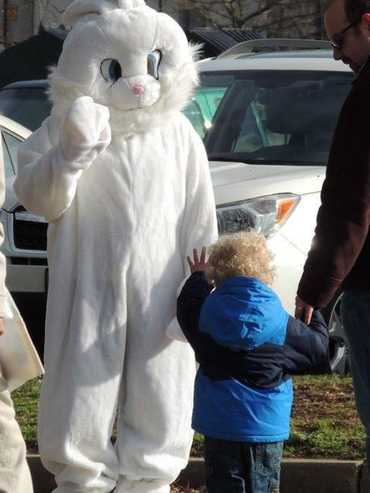Kiwanis member dressed in white Easter bunny costume with boy in blue jacket.