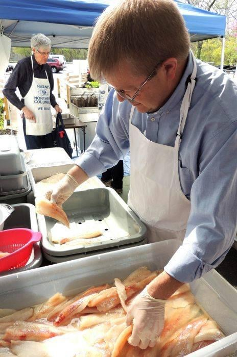 Man wearing apron dipping dipping fish in flour.
