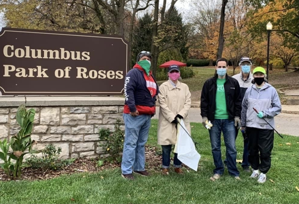 """People wearing masks standing in from of """"Columbus Park of Roses"""" sign."""