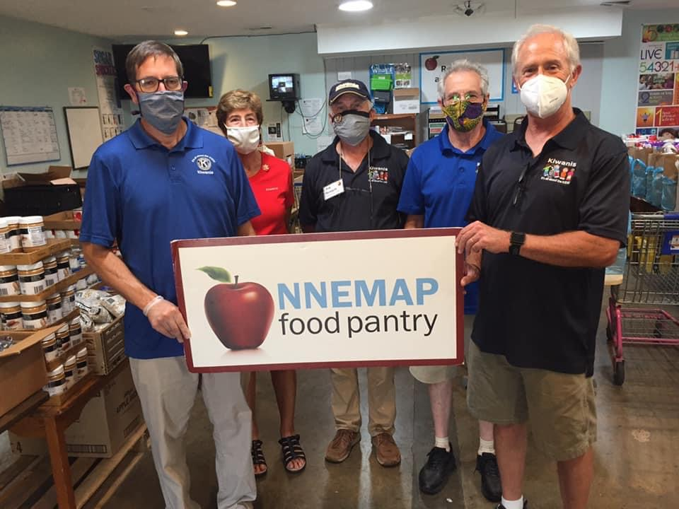 Four men and one woman, wearing masks and Kiwanis shirts of different colors, holding NNEMAP food pantry sign.