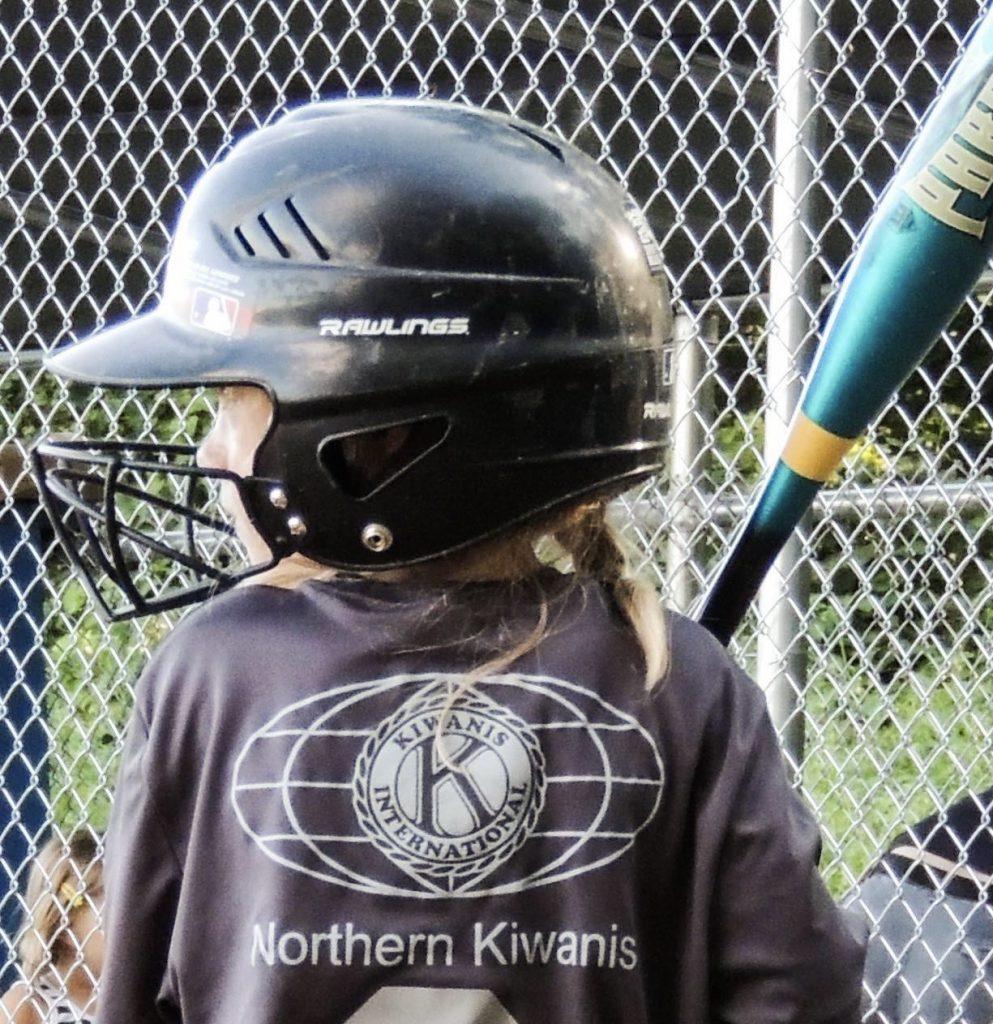 Girl with baseball bat and wearing helmet and a shirt with Kiwanis logo and Northern Kiwanis printed on shirt.