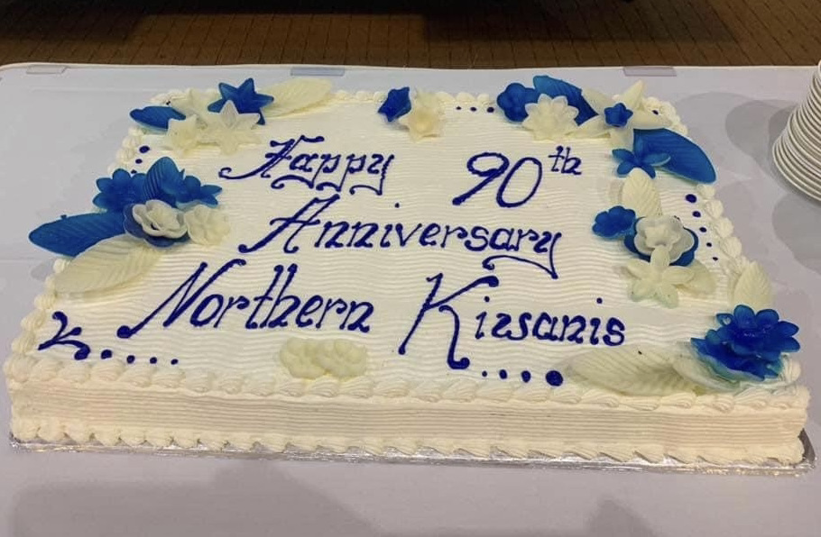 """Cake with white frosting and blue and white flowers with the inscription """"Happy 90th Anniversary Northern Kiwanis""""."""