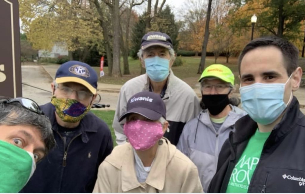 People wearing masks standing in a park